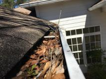 Before a completed gutter cleaning service project in the area